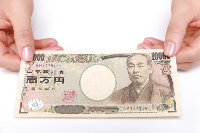 両手で持っている一万円札