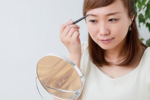 メイクをしている女性と鏡