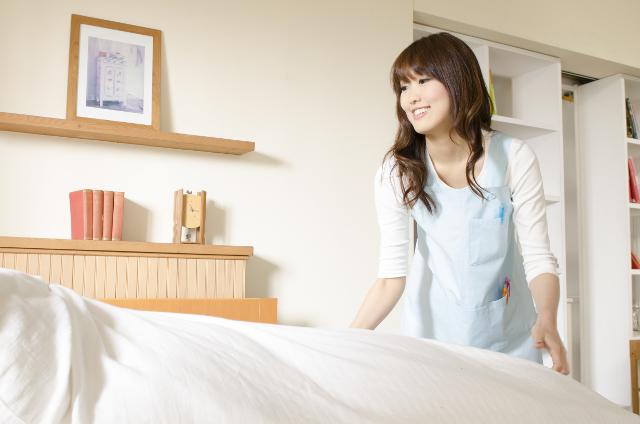 ベッドメイキングする女性
