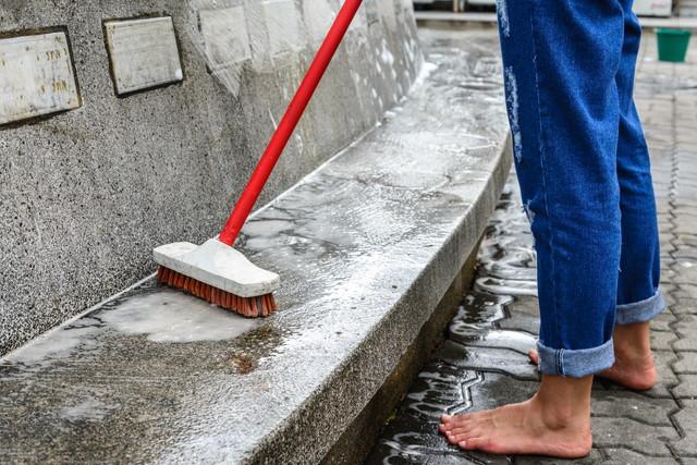 コンクリートを掃除する赤いブラシ