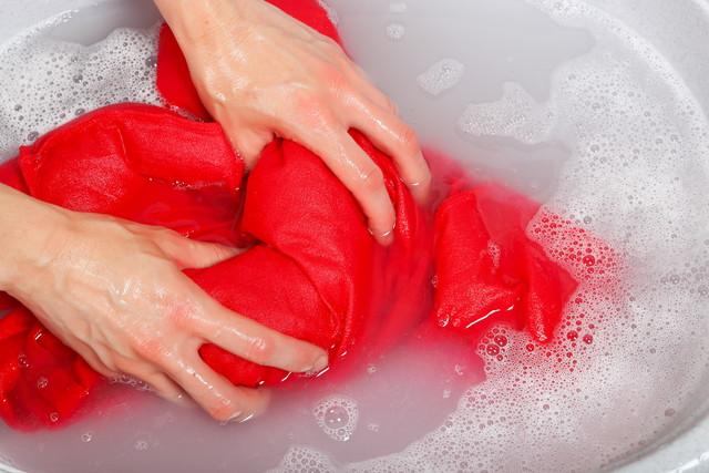 手洗いしている赤い服