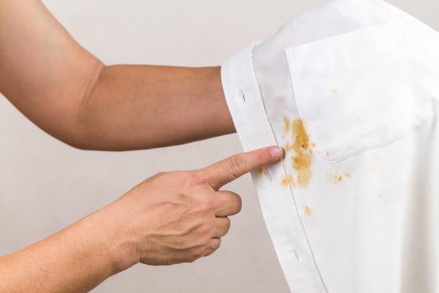 シミを指さす、白いシャツ