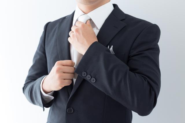 白いネクタイを結ぶ男性