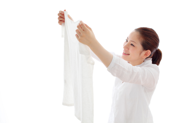 洗濯した服を見ている女性
