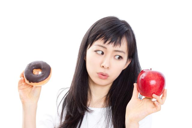 ダイエット,りんごとドーナッツで悩む女性