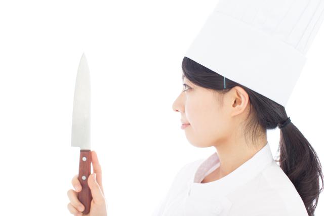 包丁を見る女性コック