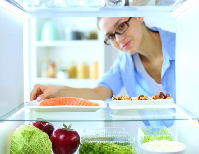 冷蔵庫の中を覗き込んでいる人