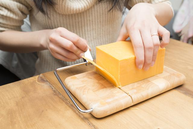 チーズを切る女性