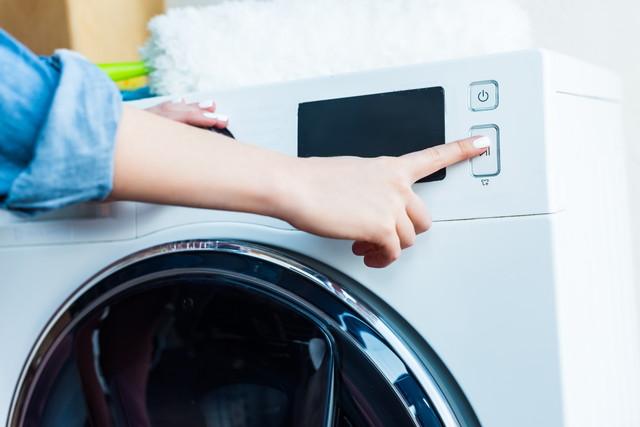 洗濯機のボタンを押す指