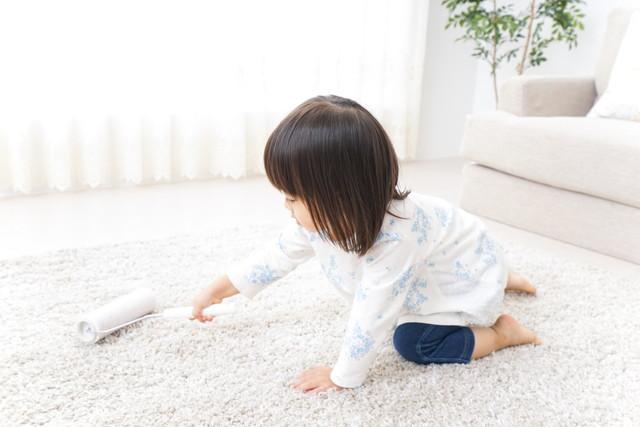 コロコロでカーペットを掃除する子供