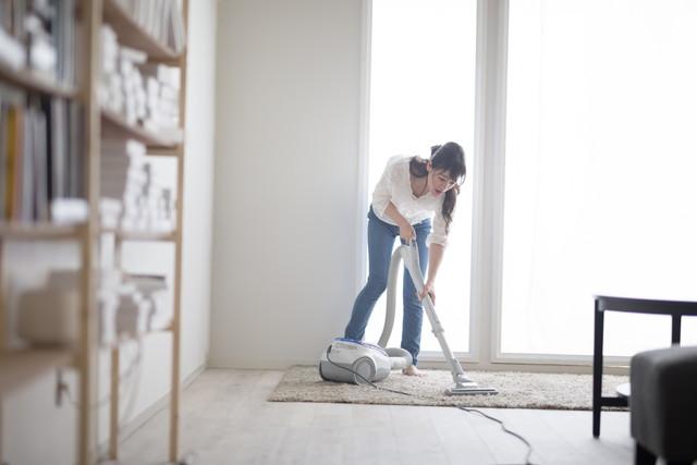 部屋で掃除機をかけている女性