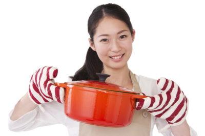 オレンジのホーロー鍋を持つ女性】