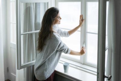 窓を閉める女性