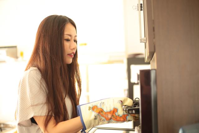 オーブントースターの網を出す女性