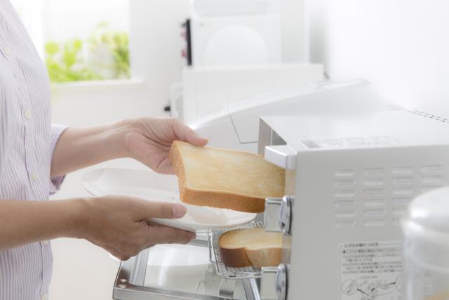 パンをトースターから出す