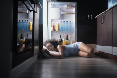 冷蔵庫を開けたまま寝ている女性
