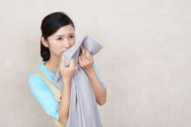 洗濯物匂いに顔をしかめる主婦