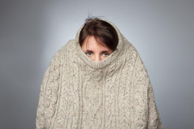 縮んだセーターを着た女性