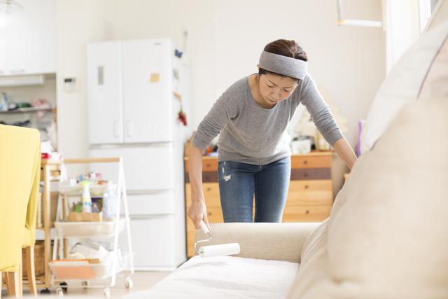 ソファーの掃除をする女性