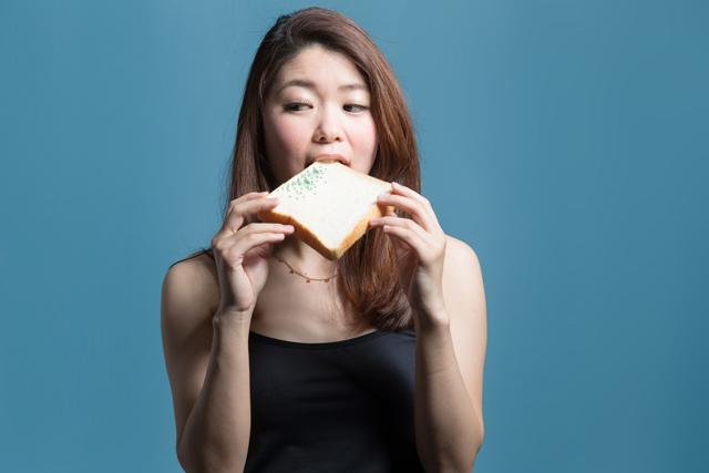 カビが生えたパンを食べる女性