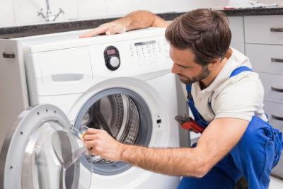 洗濯機をチェックしている人