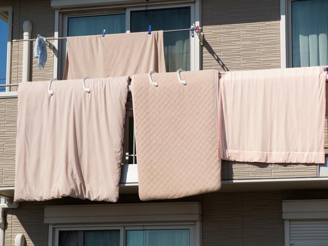 ベランダに干してあるピンクのたくさんの布団