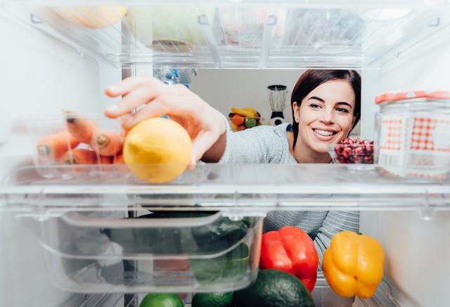 冷蔵庫の中身を取っている女性