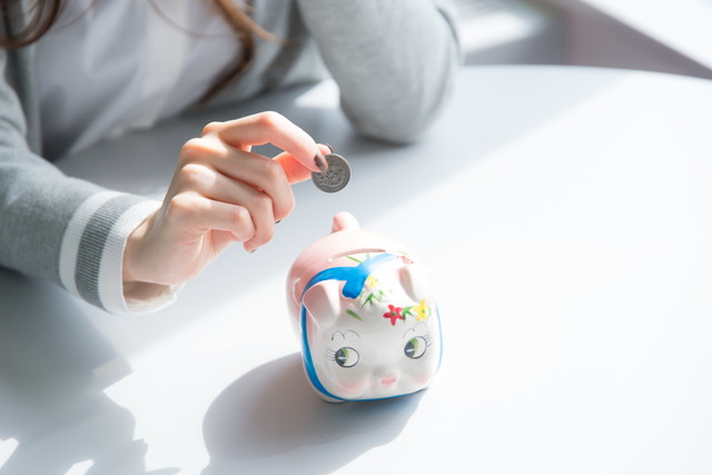 貯金箱に硬貨を入れる女性の手