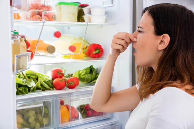 冷蔵庫の臭いに鼻をつまむ女性