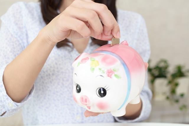 豚の貯金箱を持つ女性