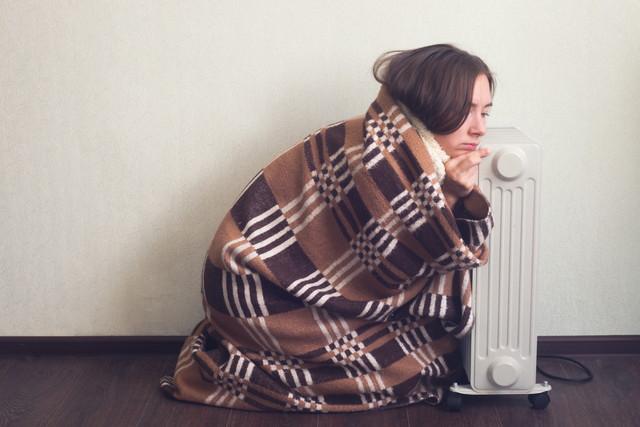 オイルヒーターで温まるのを待っている女性