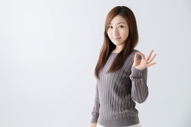 セーターを着てOKサインを出す女性