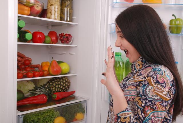 冷蔵庫の前でびっくりしている女性