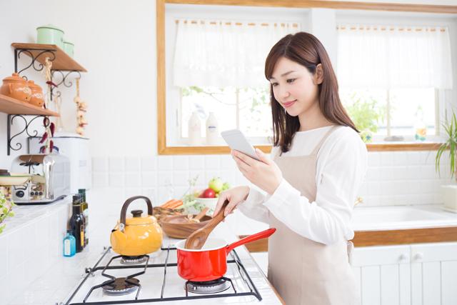 調理中にスマホを見る女性