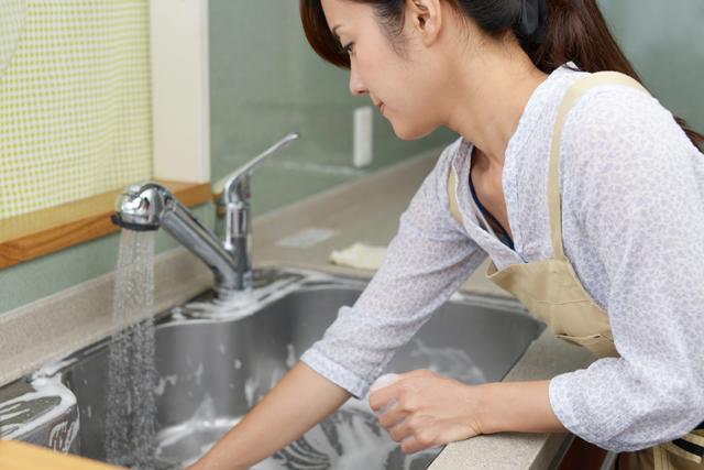 流し台を掃除する女性