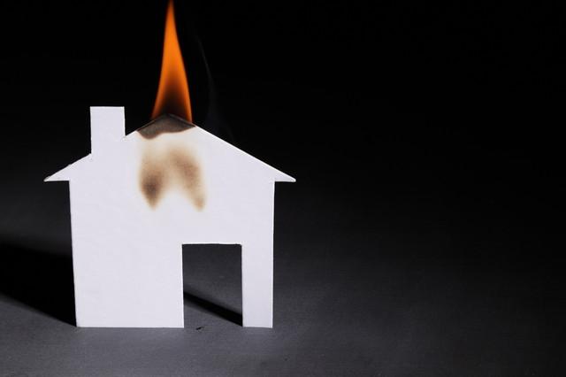 小さな紙の家の屋根を燃やすオレンジ色の炎