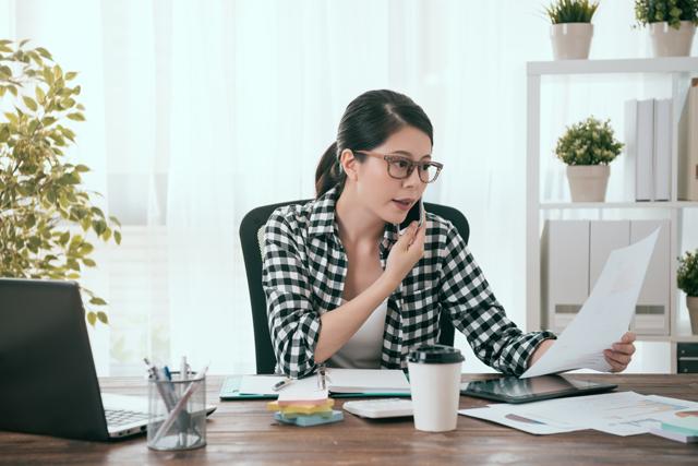 電話をしながら書類を見る女性