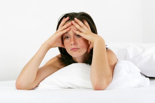 ベッドで女性が悩んでいる