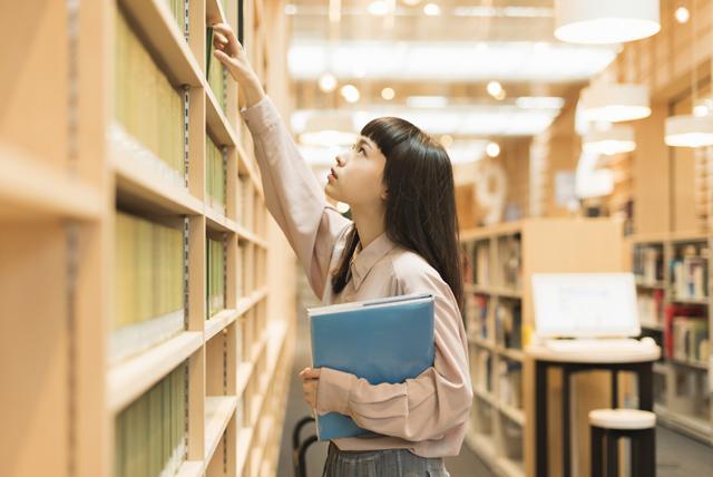 図書室で手を伸ばす女性