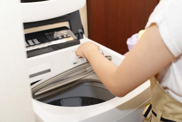 洗濯機に粉末洗剤を入れている女性