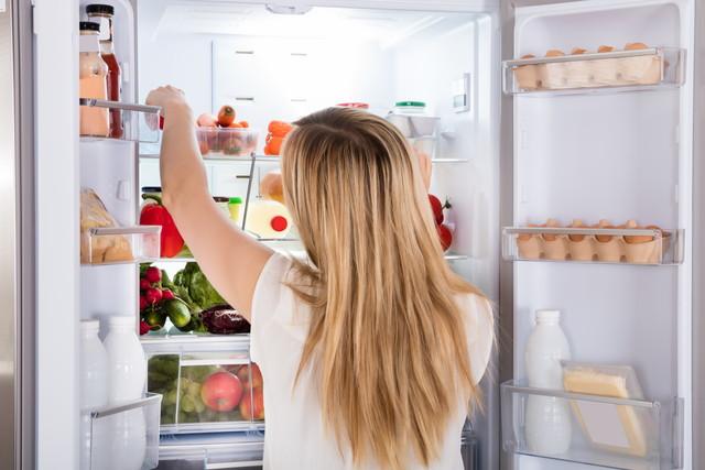 冷蔵庫の中身を探る女性
