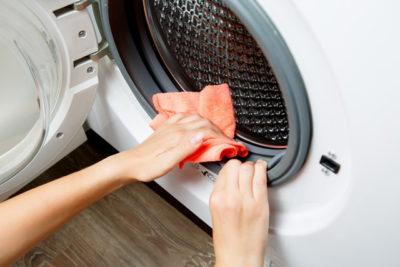 洗濯機をタオルで拭いている