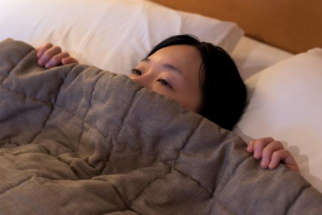 ベッドで考え事をする女性