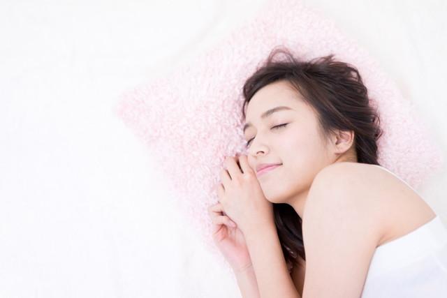 タオルを枕に女性が寝ている写真