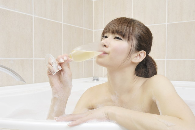 お風呂に入りながらシャンパンを飲む女性