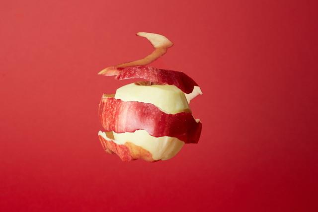 リンゴと剥かれた皮と赤い背景