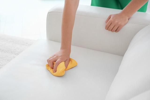 合皮製のソファーを拭く女性