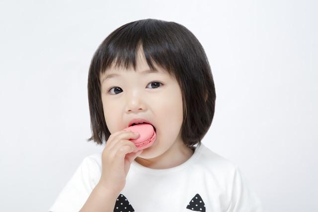 ピンクのマカロンを食べる女の子