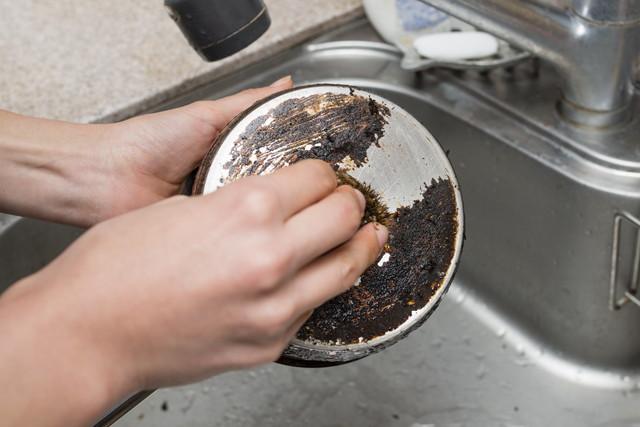 鍋の焦げ付きを磨く女性の手
