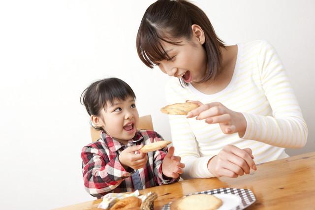 お菓子を食べる親子